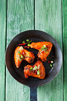 Three marinated and grilled chicken wings in cast-iron frying pan - p300m1417325 by Dieter Heinemann