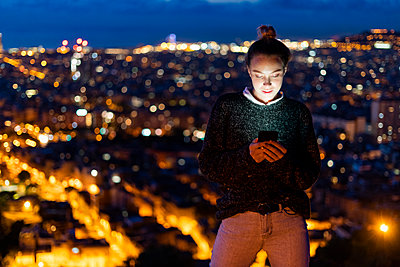 Young woman using cell phone at night above the city, Barcelona, Spain - p300m2143728 by Giorgio Fochesato