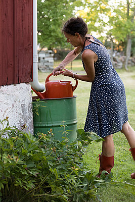 Woman filling watering can - p312m1532834 by Ulf Huett Nilsson