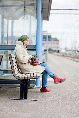 Adult woman sitting alone at train station - p312m1551883 by Johner Images