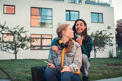 Smiling female teenager talking with each other against building - p426m2270958 by Kentaroo Tryman