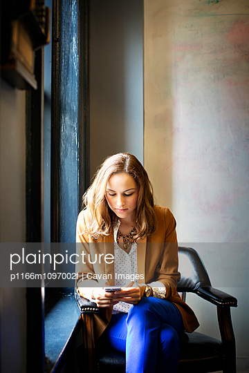 Office worker sitting on armchair by window and using mobile phone on break