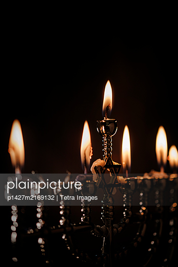 Lit candles in menorah - p1427m2169132 by Tetra Images