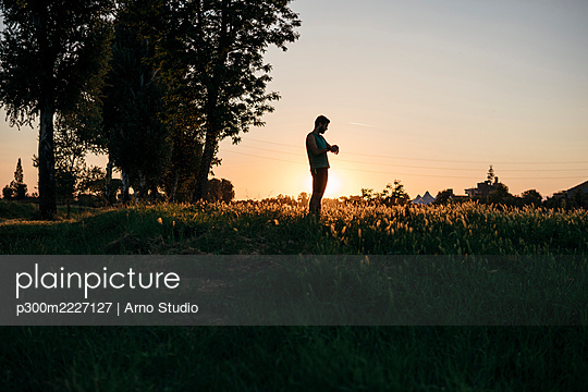 Sportsman standing on grass in park during sunset - p300m2227127 by Arno Studio