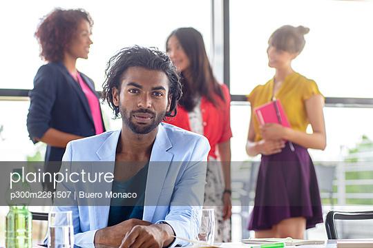 Deutschland, Bayern, München, Business, Portrait von selbstbewusstem, kreativen Mann der in Kamera schaut mit Internationalem Team in Bürogebäude - p300m2281507 von Buero Monaco
