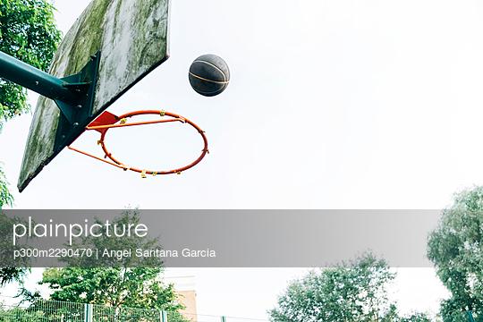Basketball over hoop at court - p300m2290470 by Angel Santana Garcia