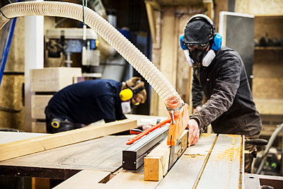 Man wearing ear protectors, protective goggles and dust mask standing in a warehouse, cutting piece of wood with circular saw. - p1100m1575734 by Mint Images