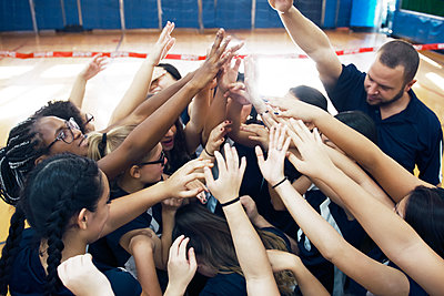 Sports teams huddling with arms raised in court - p1166m1087824f by Andrew Lipovsky