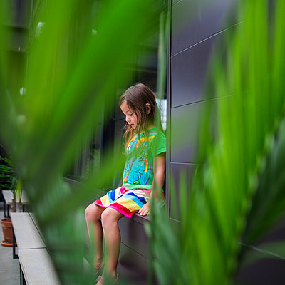 Thoughtful girl looking down while sitting on window sill seen through plants - p1166m2112675 by Cavan Images