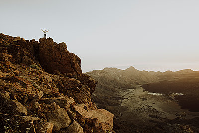 Pulled back of man standing on rock at mountain top in Mount Teide - p1166m2129926 by Cavan Images