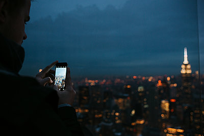 Taking pictures of New York City at night - p1507m2196541 by Emma Grann