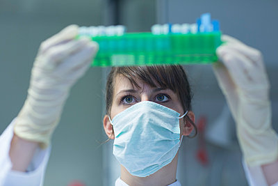 Young female natural scientist with mask and protective gloves working at  labroratory - p300m977927f by Sigrid Gombert