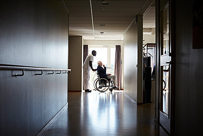 Full length side view of male nurse pushing senior man on wheelchair at hospital corridor - p426m1494019 by Maskot