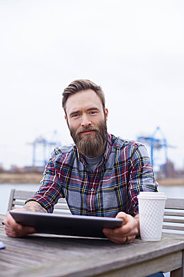 Portrait of young male designer on waterfront outside design studio - p429m1448294 by Jakob Helbig