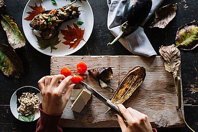 Woman slicing cherry tomatoes on rustic chopping board, overhead view of hands - p429m2052365 by Alberto Bogo