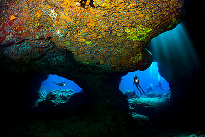 Divers are framed by the twin openings at a dive site known as Skull Cave off the Kona coast of the Big Island; Hawaii, United States of America - p442m2003588 by Dave Fleetham
