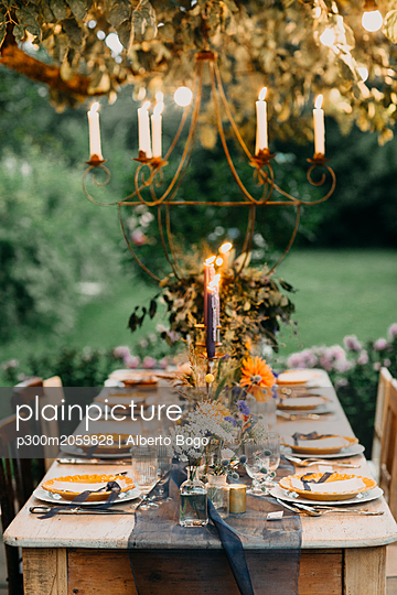 Festive laid table with candles outdoors - p300m2059828 by Alberto Bogo