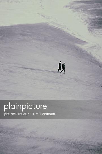 Two men walking across sandy beach at low tide - p597m2150397 by Tim Robinson