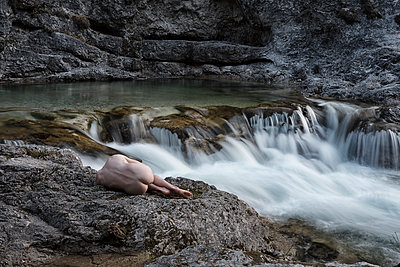 Naked man lies huddled on the river - p1383m2020750 by Wolfgang Steiner