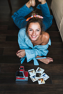 Portrait of happy young woman lying on the floor with instant photos of herself - p300m2029829 by Kike Arnaiz