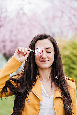 Smiling woman covering eye with flowers in springtime - p300m2274824 by Eva Blanco