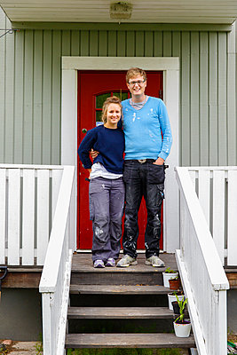 Sweden, Sodermanland, Portrait of young couple standing on porch  - p352m1079185f by Christian Ferm