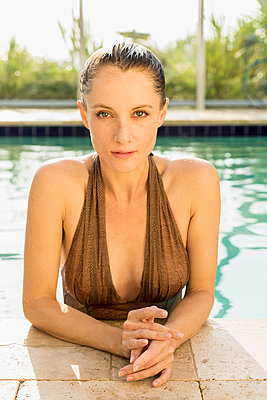 Caucasian woman poolside in swimming pool - p555m1305582 by Mark Edward Atkinson