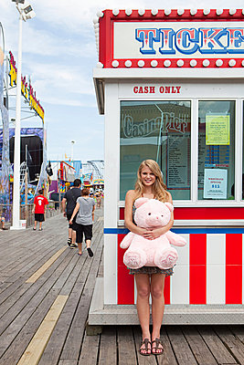 Teenage girl by ticket booth with teddy bear - p9244786f by Image Source
