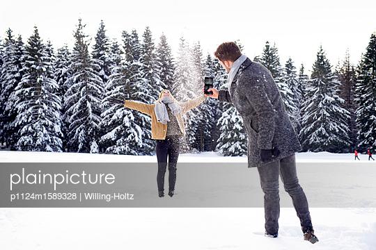 Junges Paar macht eine Schneeballschlacht - p1124m1589328 von Willing-Holtz