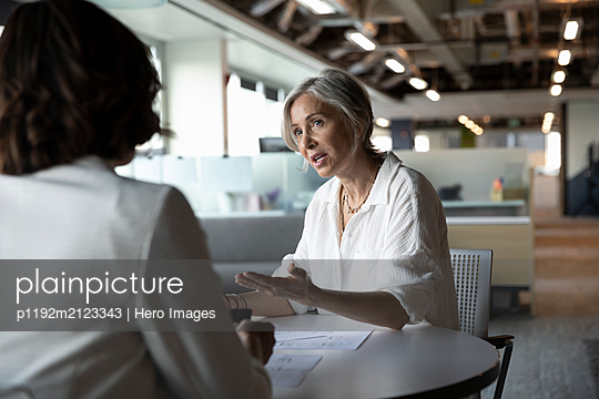 Senior woman discussing with financial advisor - p1192m2123343 by Hero Images