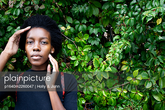 African woman in front of green leaves, portrait - p1640m2260047 by Holly & John