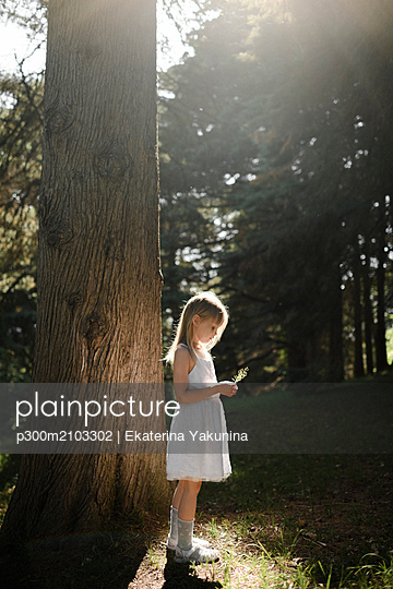 Little girl in white dress standing at a tree - p300m2103302 by Ekaterina Yakunina