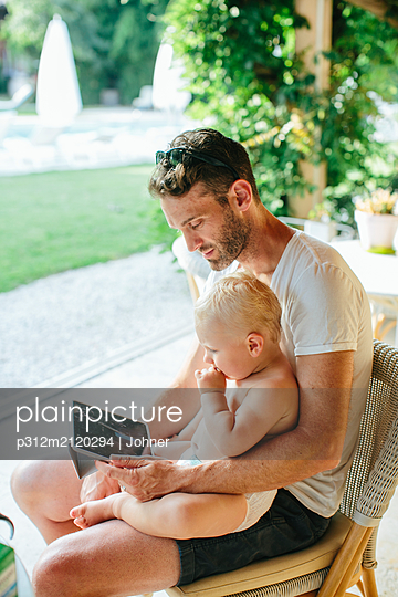 Father with toddler son using digital tablet - p312m2120294 by Johner