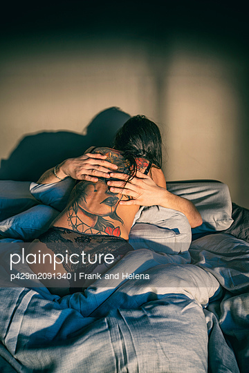 Semi-naked hipster couple in bed - p429m2091340 by Frank and Helena