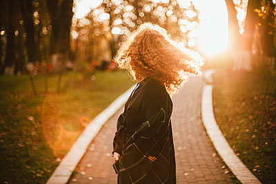 Young red head woman tossing hair while walking in park in autumn - p1166m2205795 by Cavan Images