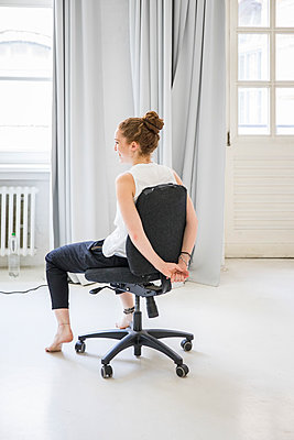 Woman on office chair - p276m2110723 by plainpicture