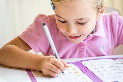 Smiling little girl writing alphabet - p300m2012620 by Jana Fernow