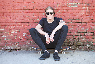 Skater sitting on board - p9245216f by Image Source