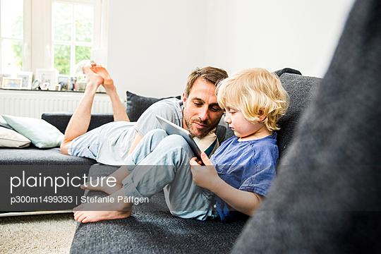 Father and little son relaxing together on the couch looking at tablet