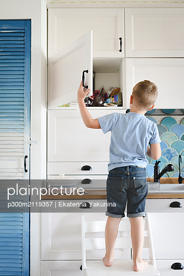 Back view of little boy standing on chair in the kitchen looking into cupboard - p300m2119357 by Ekaterina Yakunina