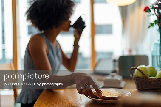 Young woman having breakfast on table at home - p300m2213955 by Boy photography