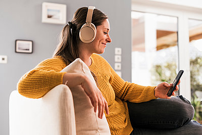 Woman listening music through wireless headphones while sitting on sofa at home - p300m2268225 by Uwe Umstätter