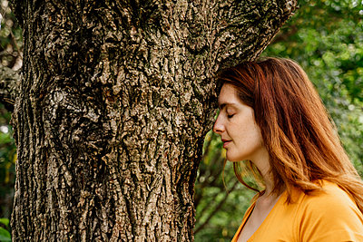 Relaxed woman with eyes closed by tree trunk in garden - p300m2287116 by VITTA GALLERY