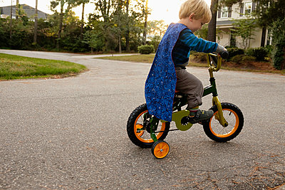 Caucasian boy riding bicycle with training wheels - p555m1410640 by Roberto Westbrook