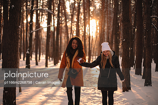 Happy girlfriends holding hands while walking in snow covered park - p1166m2268798 by Cavan Images