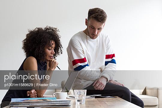 Junges, modernes Team aus Mann und Frau denken über Idee am Laptop nach  - p1301m1589629 von Delia Baum