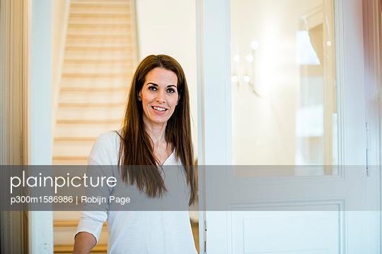 Portrait of smiling woman at home - p300m1586986 von Robijn Page