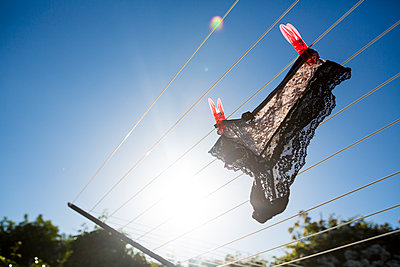 Black lace knickers hanging a clothesline - p1057m1591662 by Stephen Shepherd