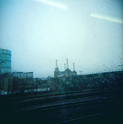 View through rainy train window of Battersea power station - p1072m829294 by Neville Mountford-Hoare