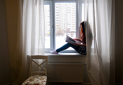 Side view of teenage girl reading book while sitting by window at home - p1166m1543578 by Cavan Social